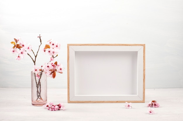 Empty picture frame and pink spring flowers.