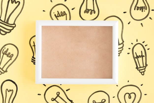 Empty picture frame surrounded with light bulbs on yellow background