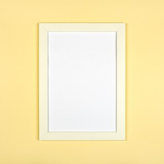 Empty picture frame on textured pastel yellow background