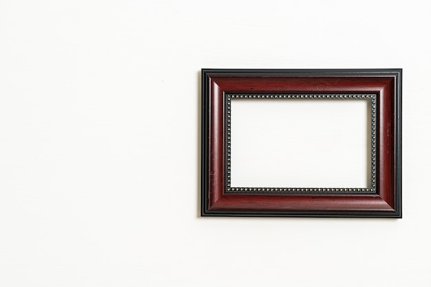 Empty picture frame on white wall background with copy space
