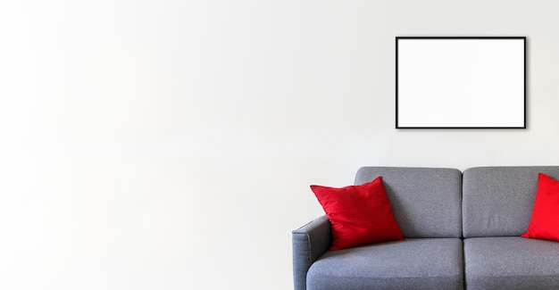 Empty picture frame on a white wall above a sofa. minimalist interior background. horizontal banner