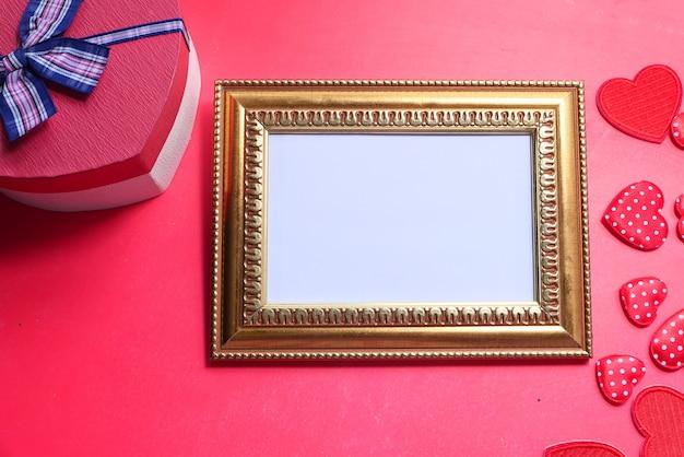 赤い背景の上のギフトボックスと空の図枠