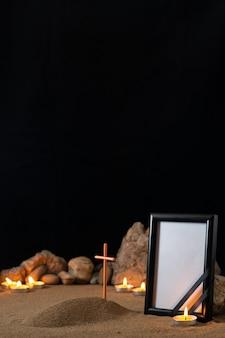 Пустая рамка для фотографий с камнями, свечами и могилой на темной поверхности