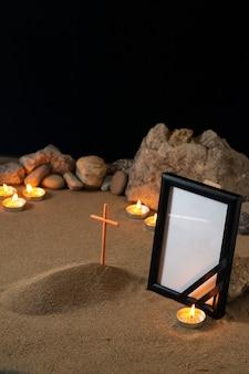 Cornice vuota con candele di pietre e piccola tomba sulla superficie scura