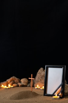 Empty picture frame with stones candles and little grave on the dark surface