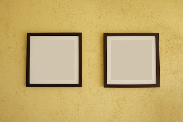 Empty picture frames on vintage yellow walls.