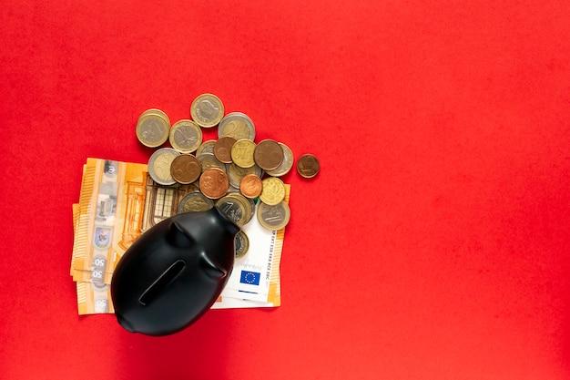 赤いテーブルの上に横に貯蓄の量が横にある空の貯金箱。お金の概念を保存