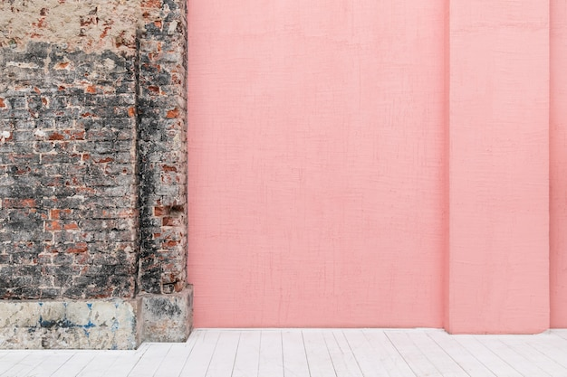 Empty pink coloured concrete wall with free copyspace in loft apartment with white wooden floor and brickwork