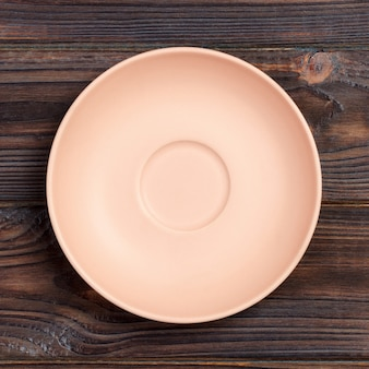 Empty pink or coral round plate on wooden table background.
