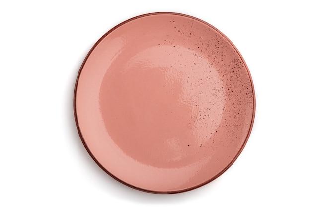 白で隔離される空のピンクの点線のセラミックプレート
