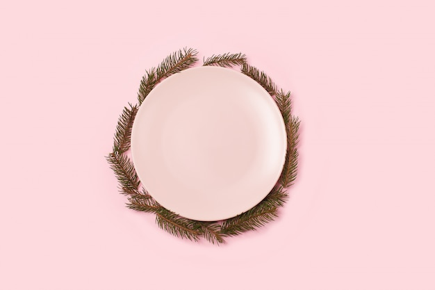 Empty pink plate and christmas tree around on pink background.