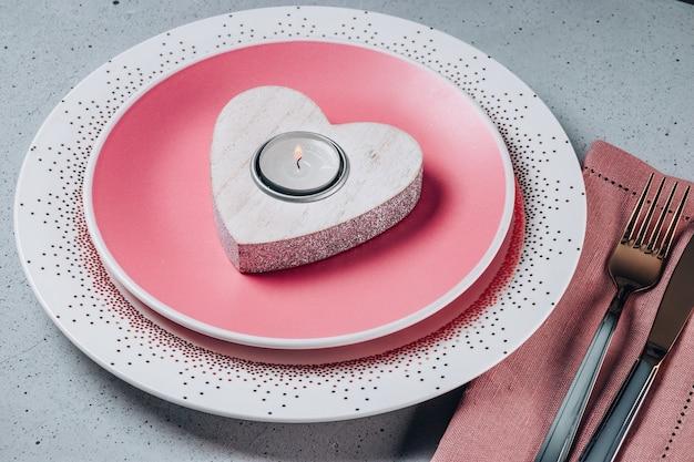 빈 분홍색 접시, 칼 붙이 및 심장 모양의 테이블에 촛불. 세인트 발렌타인 테이블 설정. 고품질 사진