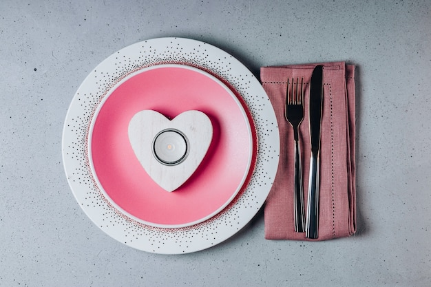 Empty pink plate, cutlery and heart shaped candle. saint valentine's day table setting. high quality photo