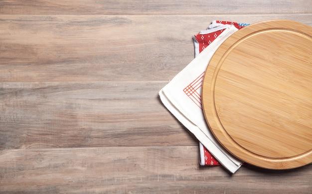 나무 배경에 빈 피자 보드와 패브릭 식탁보.