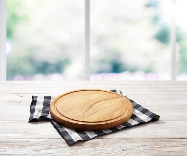 Пустая доска для пиццы и скатерть на деревянном столе с салфеткой сверху. кухонные интерьеры и лето за окном.