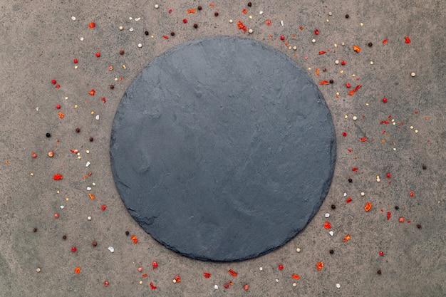 어두운 콘크리트 배경에 향신료를 넣은 빈 피자 접시가 평평하게 놓여 있고 복사 공간이 있습니다.