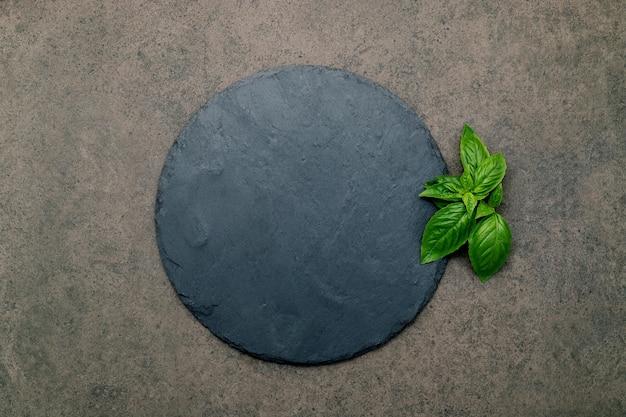 어두운 콘크리트 위에 수제 베이킹을 위한 빈 피자 플래터. 복사 공간이 있는 어두운 돌 배경 질감에 대한 음식 레시피 개념.
