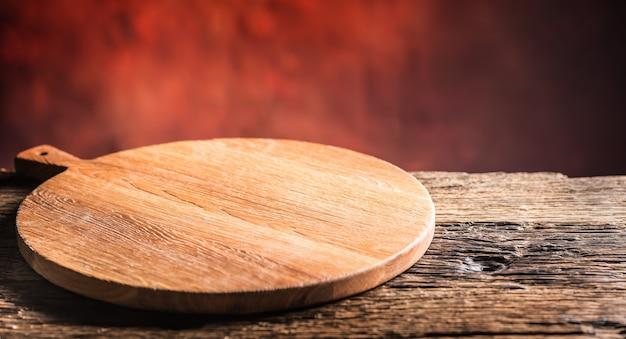 Пустая пицца круглая доска старый деревянный стол и цвет размытый фон.