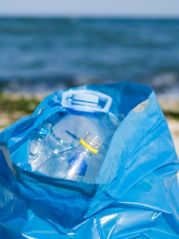 Empty plastic bottle in blue garbage bag at outdoors