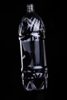 Пустая пластиковая бутылка для переработки на темном фоне