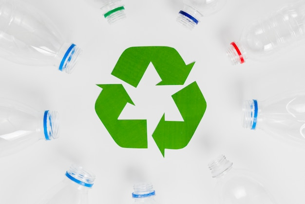 Empty plastic bottles around recycling icon