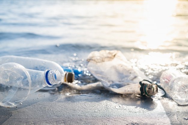 Empty plastic bottles on the beach, seashore and water pollution concept.