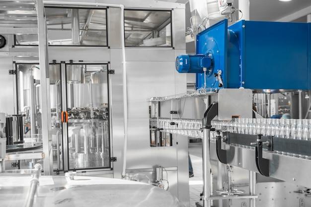 Пустые пластиковые бутылки на конвейерной ленте. оборудование на молочном заводе