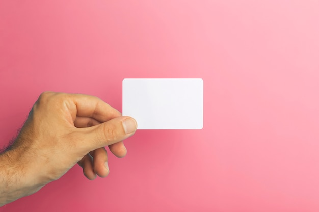 Empty plastic card in hand on colored background id or credit money card isolate high quality photo