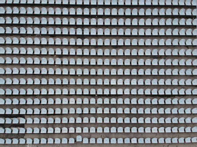 Пустые пластиковые стулья на стадионе.