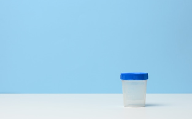 Empty plastic container for the collection of analyzes on a white table, blue background, copy space