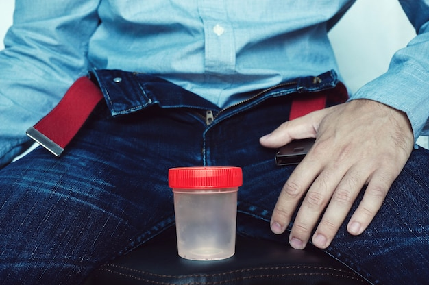 Empty plastic container for testing semen or urine, on the background of unbuttoned pants.