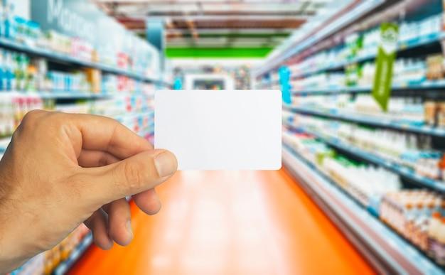 Пустая пластиковая карточка бакалеи в руке на карточке бакалеи фоне супермаркета для скидок