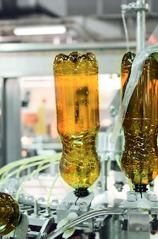 Empty plastic pet bottles in a filling machine. brewing production, abstract industrial background.