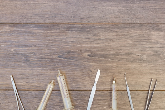 Empty plastic syringe and surgical instruments on wooden desk