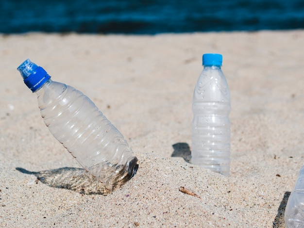 Empty plastic water bottle on sand at beach