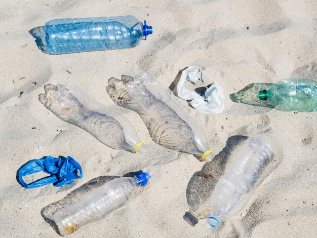Empty plastic water bottles and plastic bag on sand