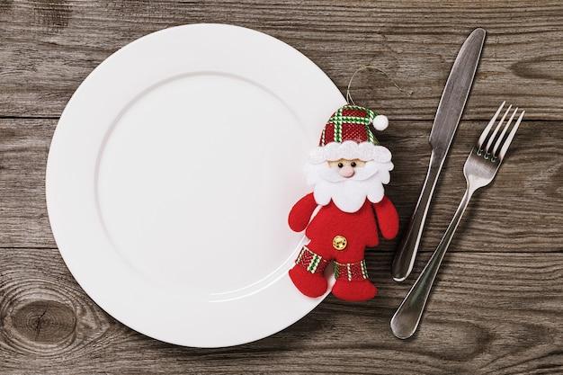 복사 공간이 있는 나무 테이블에 빈 접시와 칼 붙이 부드러운 크리스마스 장난감 산타 클로스