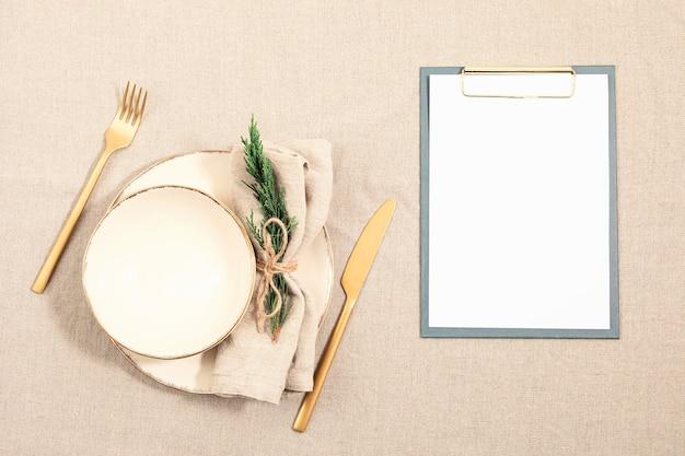 자연 중립 색상의 리넨 테이블 천으로 빈 접시와 전나무 나무 가지. 평면 위치, 평면도