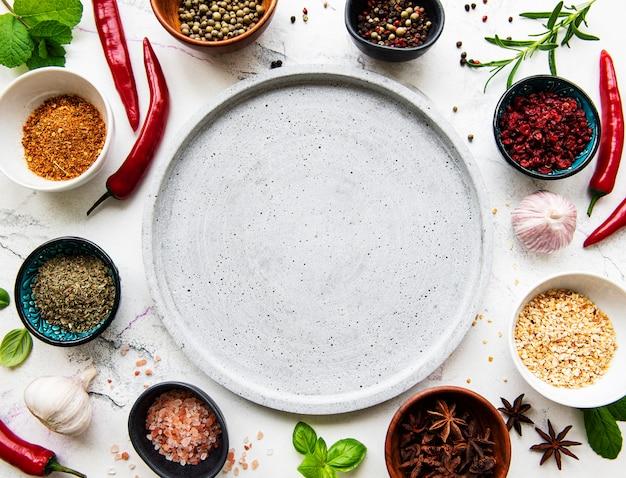 空の皿とスパイス、ハーブ、白い大理石の背景に野菜のフレーム。平面図、フラットレイアウト。