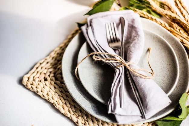 Пустая тарелка и современные столовые приборы, украшенные колосьями пшеницы