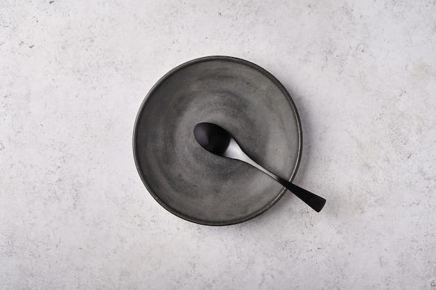Пустая тарелка и ложка темная кухонная утварь на светло-серой плоской поверхности стола с копией