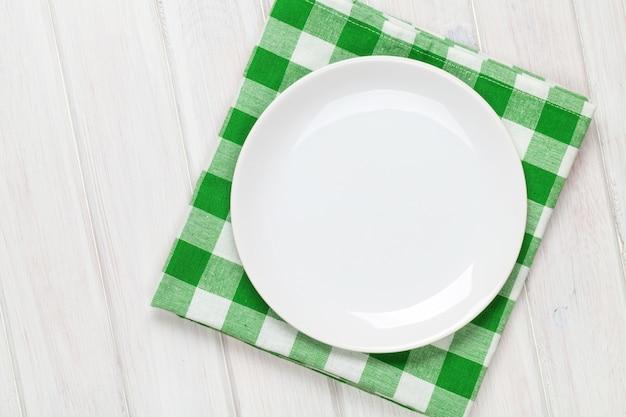 Пустая тарелка и полотенце на фоне деревянного стола. вид сверху с копией пространства