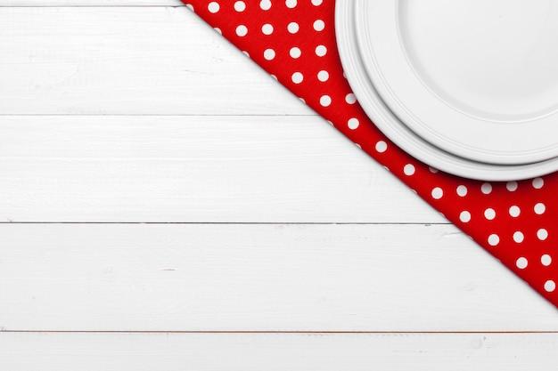 Пустая тарелка и полотенце на фоне деревянный стол.