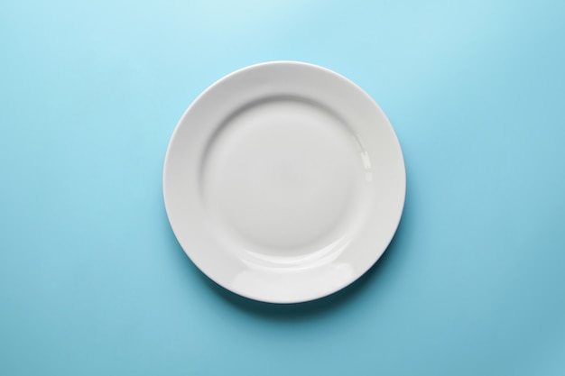 Empty plate on blue background, copy space. restaurant business went broke concept. visitor of an luxury restaurant is waiting for an order.