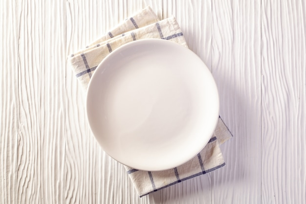 Empty plate on checkered tablecloth on white wooden table