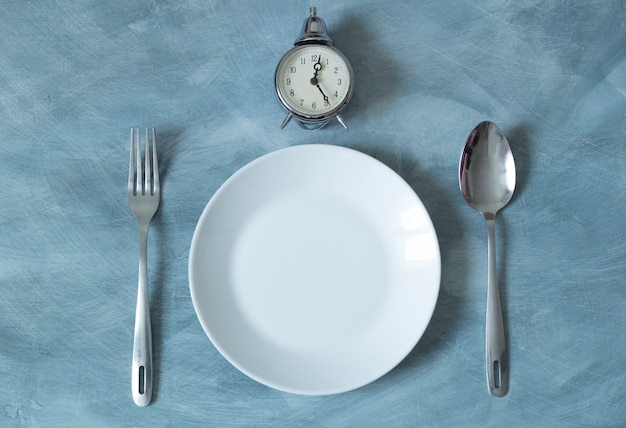 Empty plate and clock with spoon and fork for food. lunchtime.