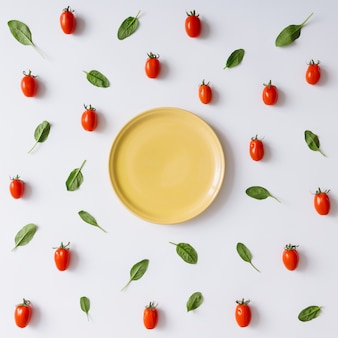 Empty plate concept with cherry tomatoes and basil leaves pattern. flat lay.