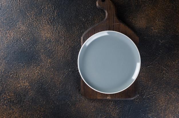 空の皿、夕食または昼食のためのカトラリー、暗いテーブル、上面図。濃い色のランチテーブル置き場設定。