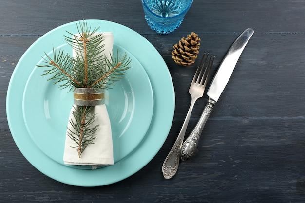 Пустая тарелка, столовые приборы, салфетка и стекло на деревенском деревянном фоне. концепция сервировки рождественского стола