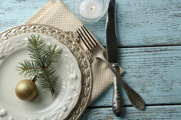 素朴な木製のテーブルに空の皿、カトラリー、ナプキン、ガラス。クリスマステーブル設定の概念